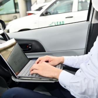 車内でパソコンをする手元